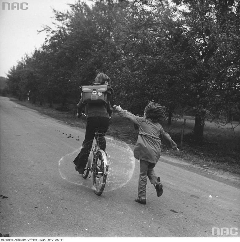 """Dziewczyna z tornistrem jedzie na rowerze """"Traper Junior"""". Za nią biegnie dziewczynka"""