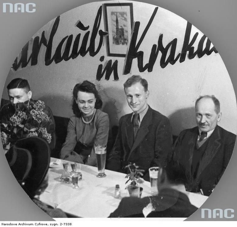 """Restauracja - wnętrze. Widoczni siedzący przy stole goście.  <font color=""""blue""""><a href="""" www.audiovis.nac.gov.pl/obraz/10463/689be1edd04d4dfabffb733d902f88e5/""""><b>Zobacz zdjęcie w zbiorach NAC</b></a> </font>"""