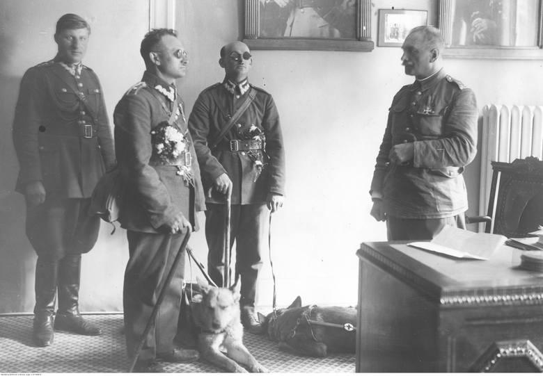 Chorąży Mikołaj Waloszewski (na pierwszym planie) i starszy ułan Stanisław Grabarek (w głębi) z psami u generała Felicjana Słowoja Składkowskiego. Z lewej adiutant wiceministra kpt Marian Idzik