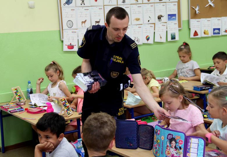 """Uczniowie klas pierwszych otrzymują kolorowanki """"Straż Miejska Dzieciom""""."""
