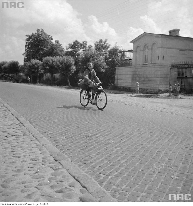 """Harcerz jadący rowerem wyposażonym w silnik doczepny """"Gnom"""" z bagażem turystycznym na bagażniku"""