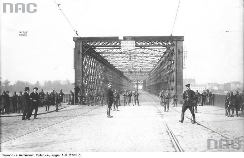 Posterunek wojskowy przy wjeździe na Most Kierbedzia od strony Pragi. Na pierwszym planie widoczni są policjanci strzegący wjazdu na most.