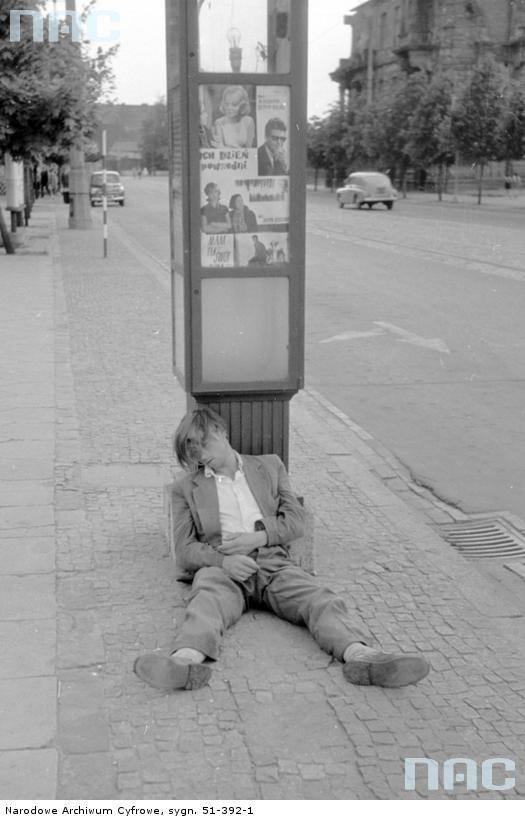 """Pijany mężczyzna śpiący na chodniku, opierający się o podświetlany słup ogłoszeniowy.<br /> <font color=""""blue""""><a href="""" http://www.audiovis.nac.gov.pl/obraz/151624/2f9408cf38524e55bd83a3c2c0ecaa5c/""""><b>Zobacz zdjęcie w zbiorach NAC</b></a> </font>"""