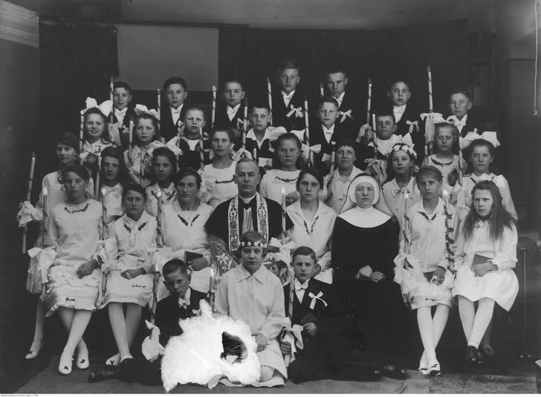 <strong>1928 rok</strong><br /> <br /> W latach 20. w modzie - także i tej komunijnej - pojawiły się krótsze sukienki o prostym kroju, nierzadko z obniżonym stanem. Coraz częściej we włosy wpinany był welon lub kokarda.