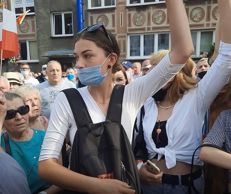 Aktywistki Młodzieżowego Strajku Klimatycznego trzymają transparent podczas wiecu Andrzeja Dudy na Rynku Kościuszki w Białymstoku