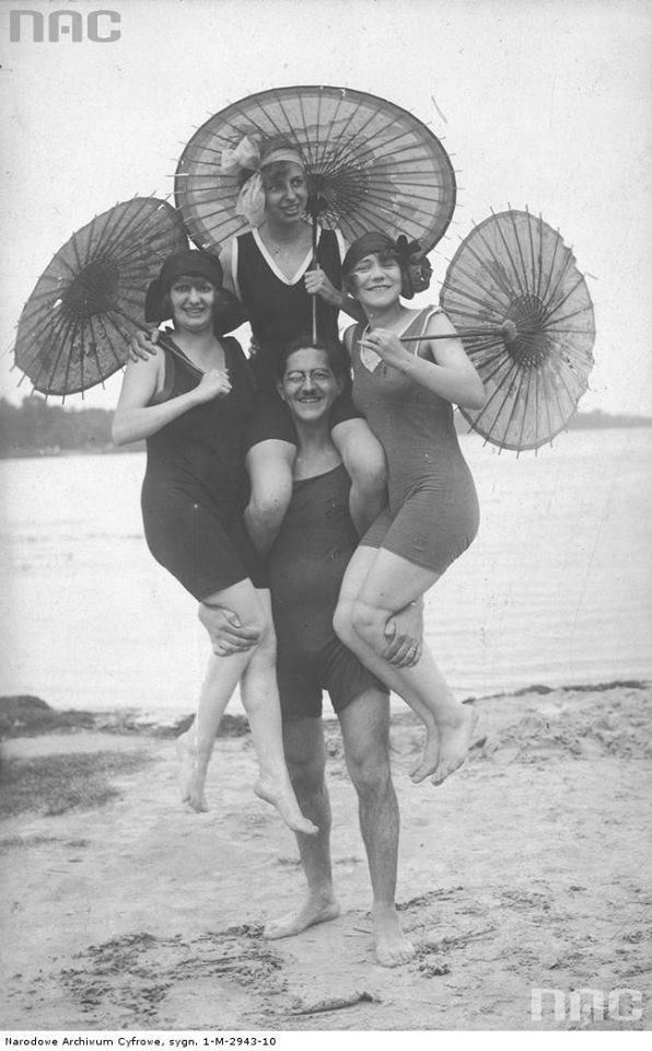 Model z modelkami na rękach pozujący na plaży w strojach kąpielowych