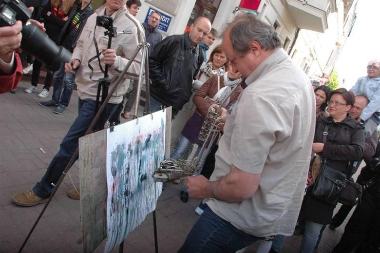"""Adam Garnek """"gra"""" na urządzeniu przypominającym saksofon. Lecz zamiast dźwięków wydobywa się z niego różnokolorowa farba. Happening"""