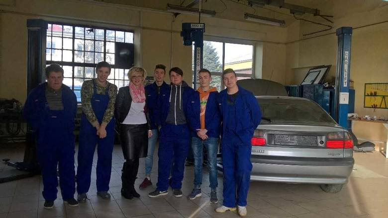 Dorota Lenart z uczniami klasy 2 - przyszłymi mechanikami pojazdów samochodowych, w specjalistycznej szkolnej pracowni .