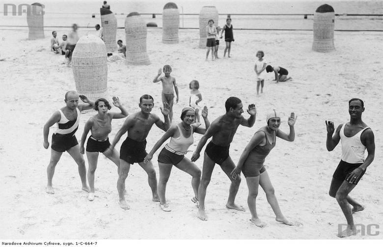Kuracjusze podczas lekcji tańca na plaży prowadzonej przez czarnoskórego instruktora.
