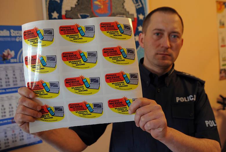 Policjant Andrzej Szajbe prezentuje praktyczne naklejki-przypominacze.