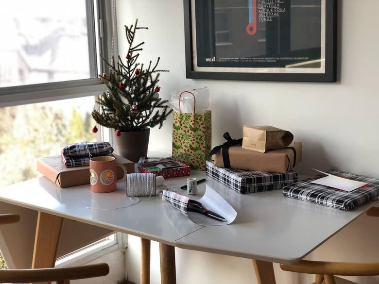 Praktyczne prezenty do domu na Mikołajki. Na zdjęciu: biurko i pakowane prezenty