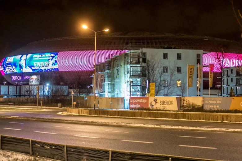 Taki widok na Tauron Arenę Kraków wyłania się od strony alei Pokoju i jej skrzyżowania z ulicą Lema. Budynki zasłaniają halę. Ta z kolei wieczorami z