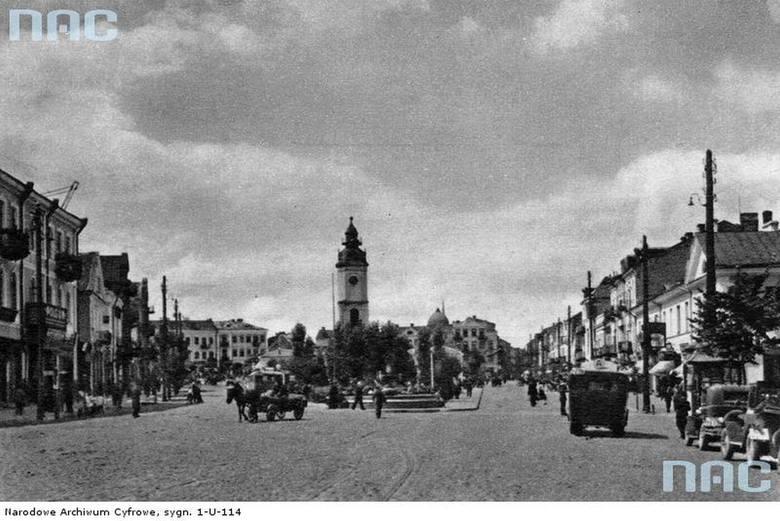 Rynek Tadeusza Kościuszki. W głębi widoczny ratusz miejski. Na ulicach widoczne samochody i furmanki. Zdjęcie zrobione w latach 1918 - 1939.