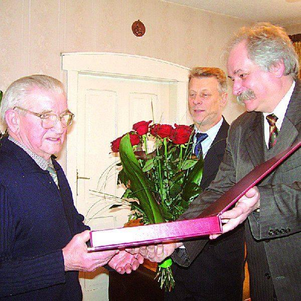 Zygmunt Przybylak odbiera pamiątkowy grawerton z rąk  przewodniczącego Rady Miejskiej Nakła Andrzeja Jedynaka.  Chwilę potem kwiatami obdarował  jubilata