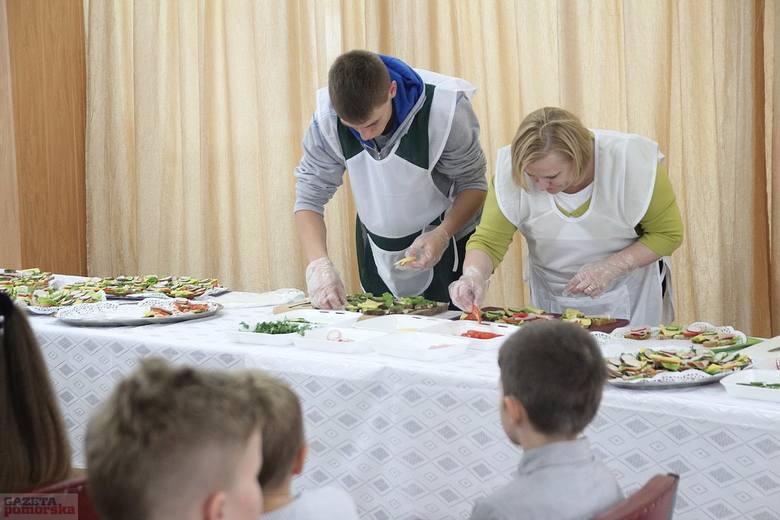 Zawodnicy przygotowują kanapki dla uczniów szkoły podstawowej