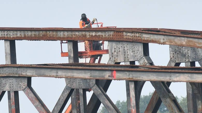 Na miejscu budowy pracuje ciężki sprzęt i spawacze, którzy również demontują konstrukcję.