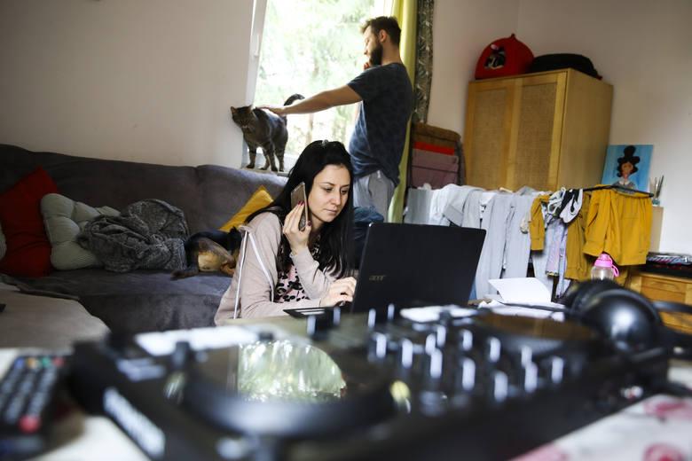 """Katarzyna Mucha jest agentką nieruchomości, w """"normalnym życiu"""" ma w pracy kontakt z ludźmi. Teraz pracuje w swoim mieszkaniu.  W tle jej chłopak Michał"""