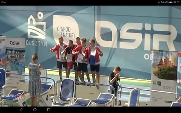 Sztafeta 4x100 zmiennym z trenerem Piotrem Wojciszko na podium