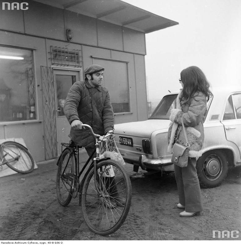 """Rolnik z zakupami na rowerze """"Goplana"""" rozmawia z kobietą przed klubokawiarnią"""