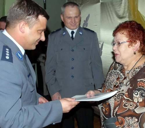 Pani Ela obiera list gratulacyjny z rąk zastępcy powiatowego komendanta Ireneusza Winnickiego. W środku stoi szef komisariatu z Pełczyc asp. Gerard