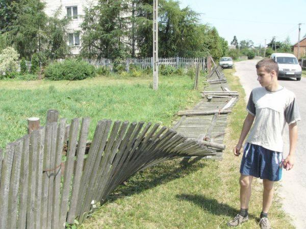 Paweł Pakosz przy powalonym na ziemię drewnianym płocie jego domu.