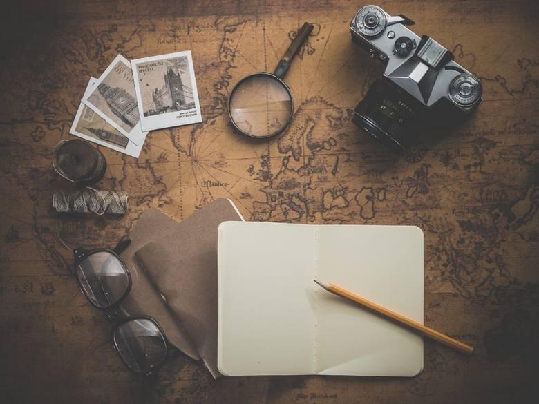 Na mapie leżą okulary, lupa, notatnik, aparat fotograficzny.