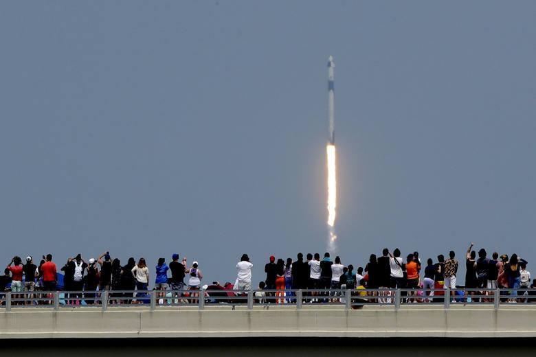 Ludzie oglądają start rakiety Falcon 9 z mostu w Titusville na Florydzie