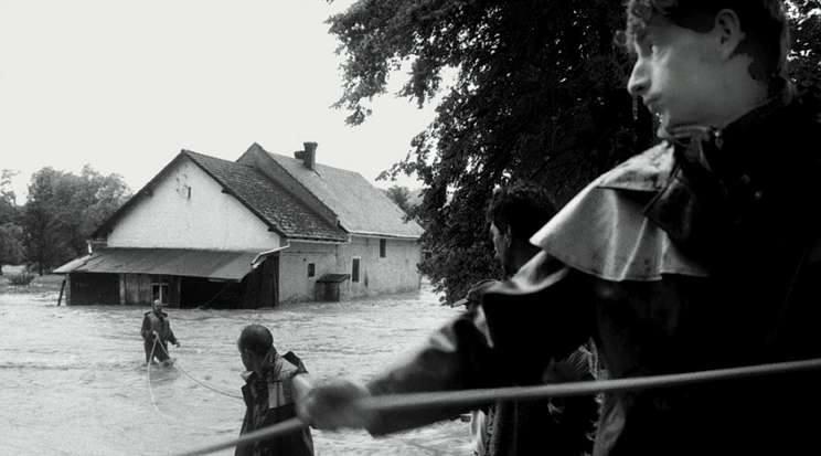 Opawica. 7 lipca 1997. Opawica po stronie polskiej i Opawice po czeskiej. Mala rzeczka zmieniła swój bieg i kilka domów we wsi po obu stronach zostało odciętych od drogi. Na zdjęciu strażacy próbują dostać się przez silny nurt do jednego z domów.