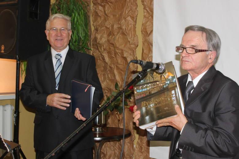 Jerzy Derenda wręcza Henrykowi Plotkowskiemu książkę o Bydgoszczy, gdzie znajdują się  liczne wzmianki o Aleksandrowie Kujawskim.