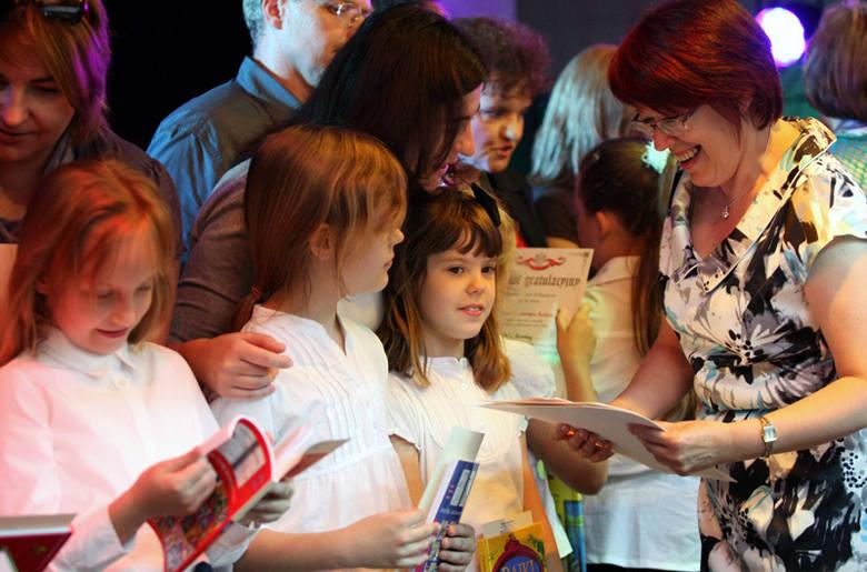 Wyróżnieni za sukcesy w nauce uczniowie i ich rodzice odbierają gratulacje od Eleonory Śledziewskiej, wicedyrektor SP 44.
