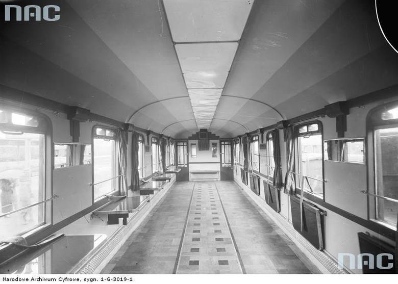 Wnętrze wagonu restauracyjnego z rozkładanymi stolikami stoliki wzdłuż ścian