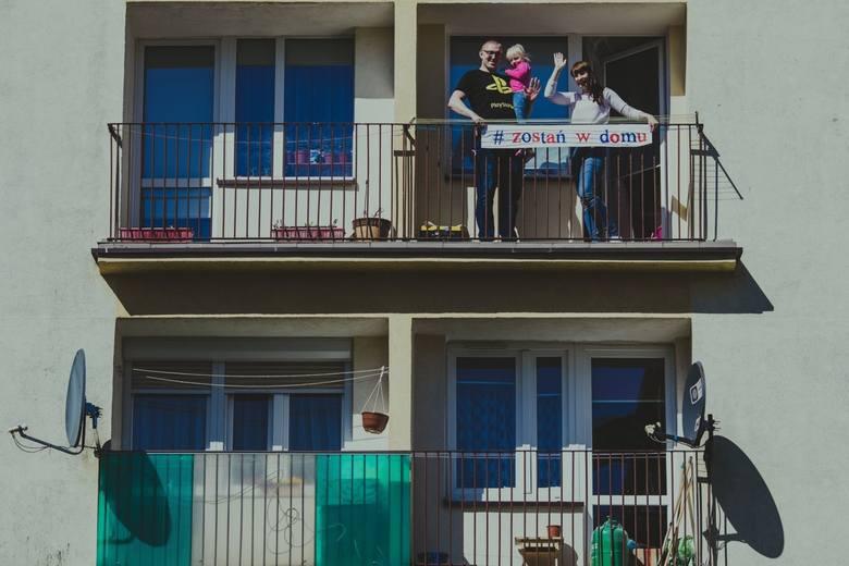 Fotograf z Człuchowa robi sesje fotograficzne w oknach i na balkonach. Z plakatami i kartkami nawołującymi do zostania w domach [zdjęcia]