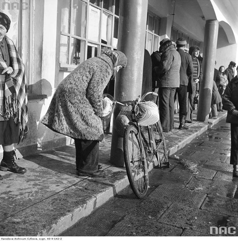 Fragment budynku sklepu od strony frontu. Przed budynkiem widoczny tłum ludzi i kobieta umieszczająca siatki i torby z żywnością na rowerze.
