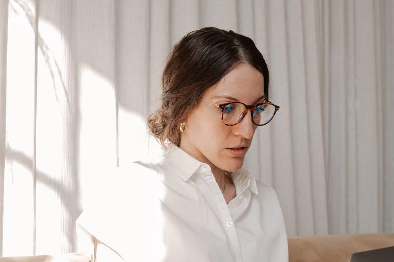 Na zdjęciu: kobieta w okularach i białej koszuli pracująca na laptopie