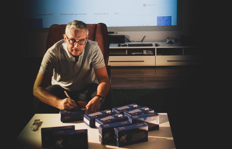 Tomasz Sikora podpisuje opakowania ze skarpetami