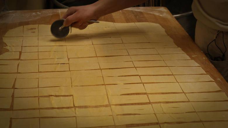 Z ciasta wycinać długie 3-cm paski, a następnie każdy pasek podzielić na prostokąty o wymiarach ok. 3x8 cm