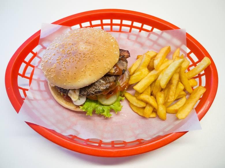 Hamburger i frytki w czerwonym koszyku przedstawione jako symbol późnego kapitalizmu.