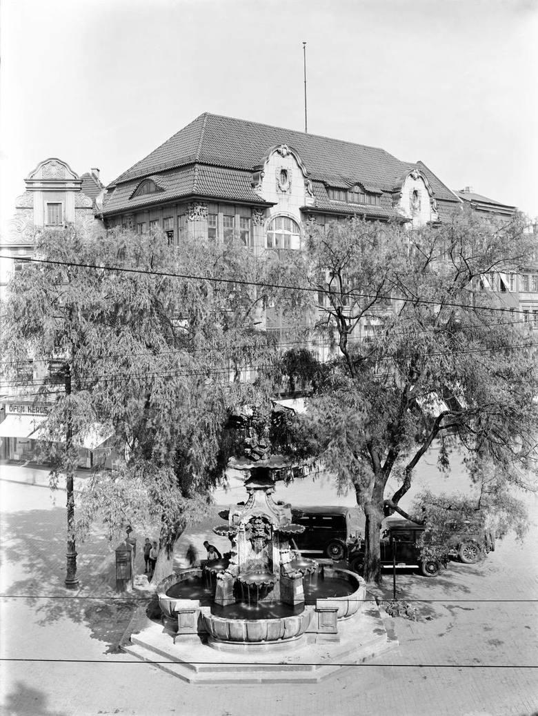 Tak przedstawiała się fontanna przed wojną. Obok wycięte nie tak dawno drzewa. Z tyłu piękna kamienica, na fundamentach której postawiono szkaradny blok