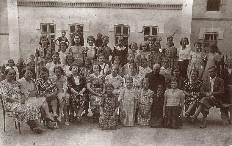 Przed szkołą w Podhajcach. Maria Wojciechowska siedzi obok księdza, z prawej strony