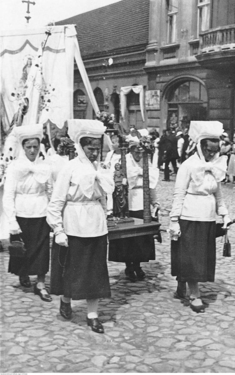 Kalisz, 1918-1937. Kobiety w charakterystycznych czepcach z okolic Błaszek niosą figurę w procesji Bożego Ciała.