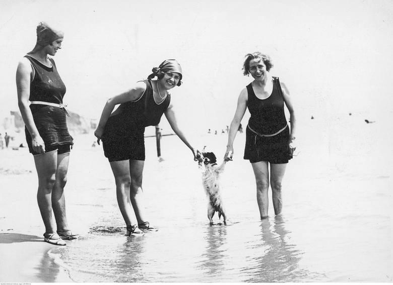 Kobiety w kostiumach kąpielowych pozują z psem na plaży.Moda sportowa na początku XX wieku dopiero się kształtowała. Stroje sportowe dla kobiet, odkrywające