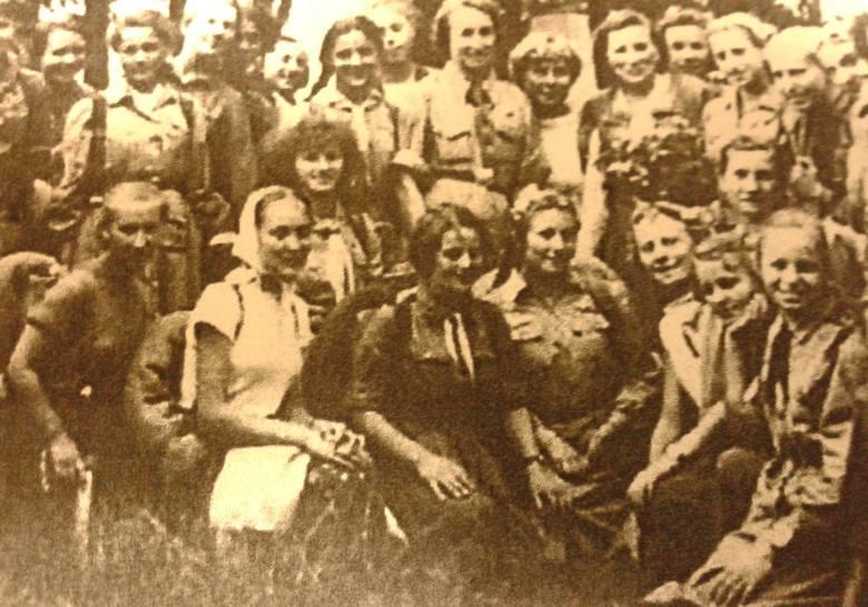 Obóz w Boguszach k. Grajewa, 28 VI - 23 VII 1957 r.  Harcerki z komendantką Bronisławą Tkaczukową (na górze z kwiatami).