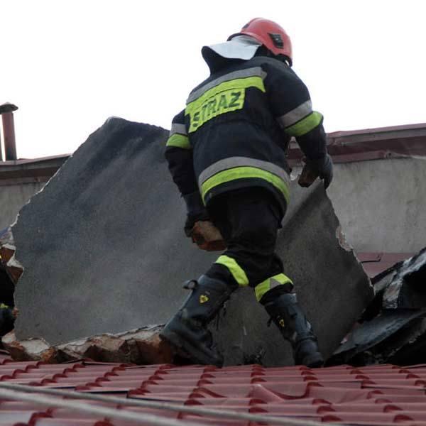 Strażacy obok przewróconego komina, który wbił się w dach.