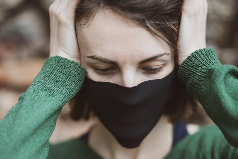 Straciłem pracę z powodu COVID-19. Co z wynagrodzeniem? Jakie prawa ma pracownik? [FAQ] Na zdjęciu: kobieta w maseczce trzymająca się za głowę