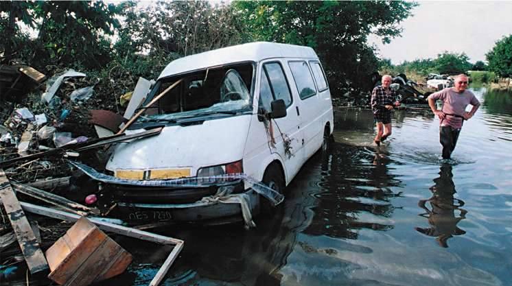 Opole 1997. Ulica Koszyka. Trzeci tydzień powodzi. Ogrodzenie ogródków działkowych jak sito wyłapało wszystko, co niosła ze sobą woda.