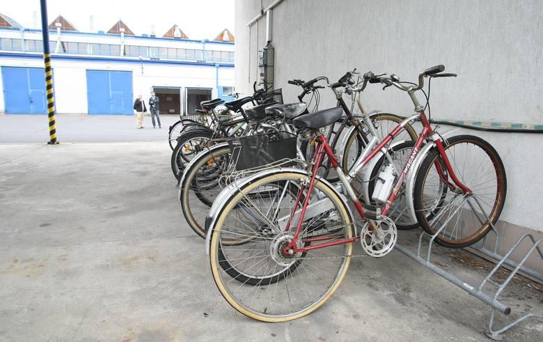 Przed budynkami znajdują się stojaki z rowerami. Pracownik bierze dowolny jednoślad.