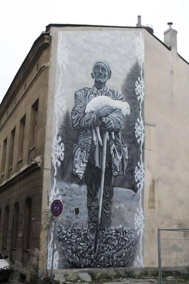 """""""Pasterz"""" to czarno-biały mural przedstawiający  postać pasterza niosącego owcę (ul. 11 Listopada 74). To realizacja grupy Projekt Etnograff, którą tworzą  Katarzyna """"Katka"""" Dyga-Szymonowicz i Maciej """"Kamer"""" Szymonowicz. Inspiracją dla autorów..."""