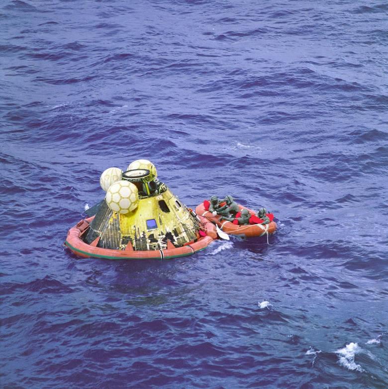 Załoga Apollo 11 czeka na transport helikopterem. Czwartym mężczyzną na tratwie ratunkowej jest pływak podwodnego zespołu  United States Navy. Wszyscy