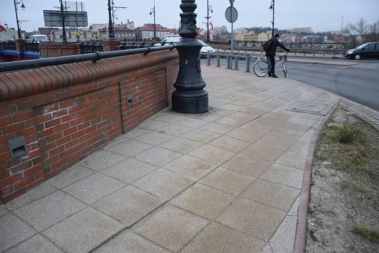 Płyty chodnikowe przy zejściu z mostu osuwają się już od lat.