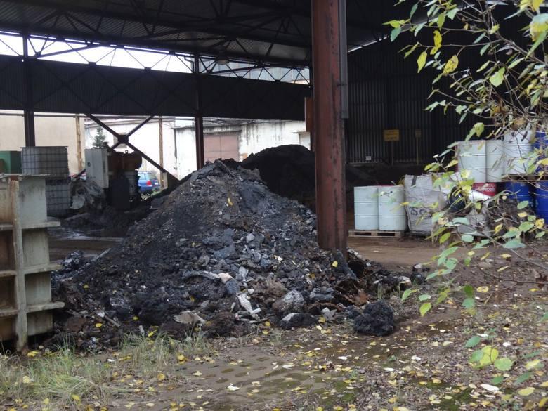 Pofabryczne pyły i inne odpady leżą na ziemi. Przy płocie stoją worki z białym proszkiem